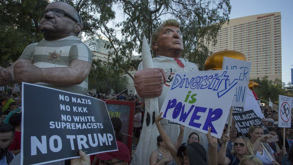 Large inflated figures of Sheriff Joe Arpaio and President Trump are seen above ant-Trump protesters outside the Phoenix Convention Center