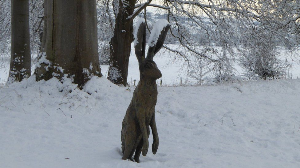 A wooden hare in the snow at Glansevern Hall Gardens, Welshpool