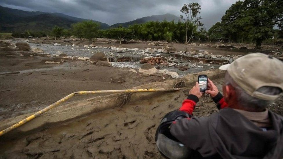 A man takes photos of La Paila river, after a mudslide due to heavy rains affected Corinto in Cauca department, southwest Colombia on November 8, 2017