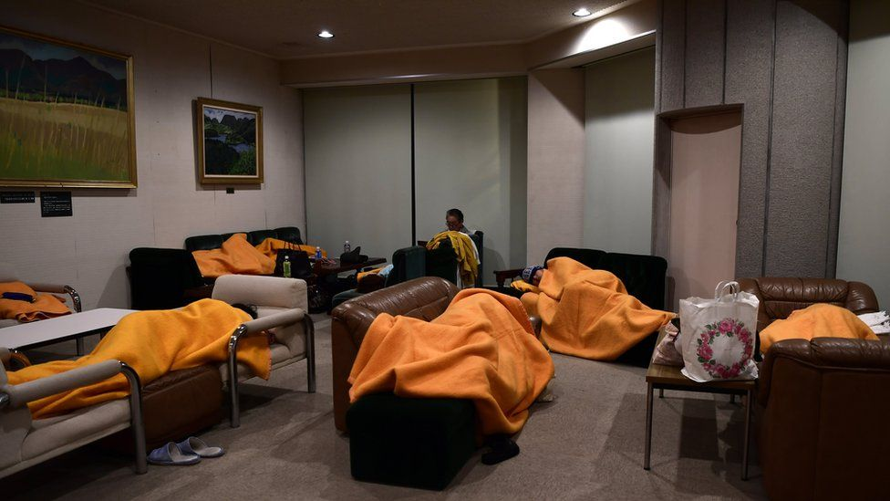 Evacuees sleep on makeshift beds in a shelter after emergency crews evacuated nearby hotel guests, in Sengokuhara, in Nakone province, Japan, 12 October 2019.