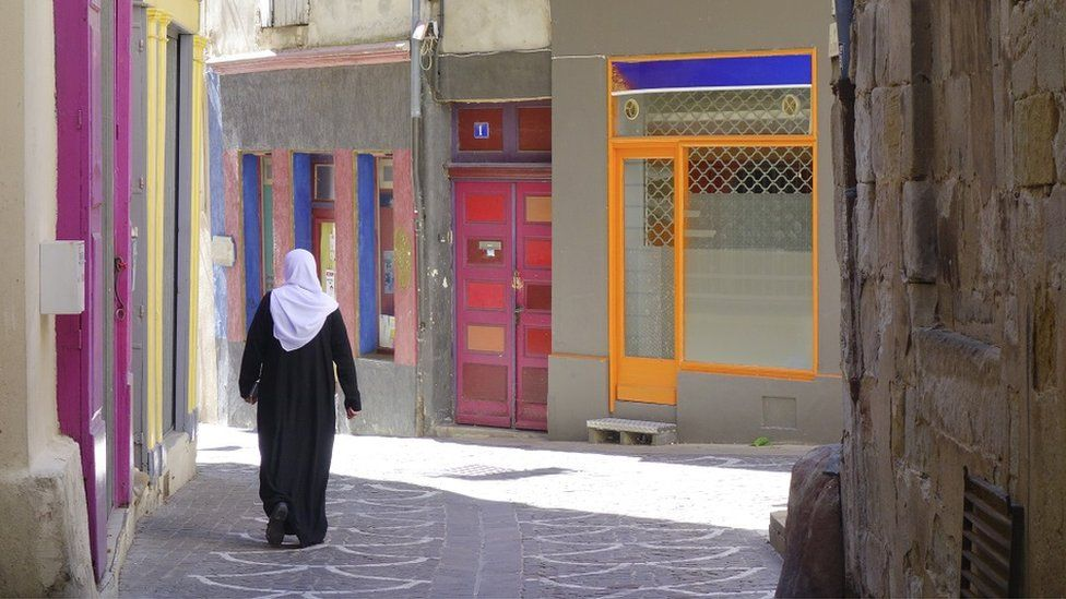 Muslim woman walks down narrow street in town of Lodève is a commune in the Hérault in the South of France
