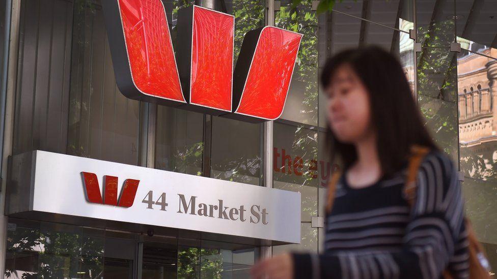 Woman walking past Westpac logo on Market street in Sydney.