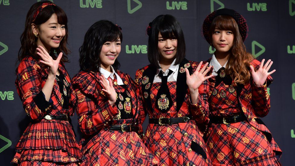 Japan's girl pop group AKB48 members pose for photographs as Japanese social networking service company Line announces the company's live streaming service in Tokyo on 10 December 2015