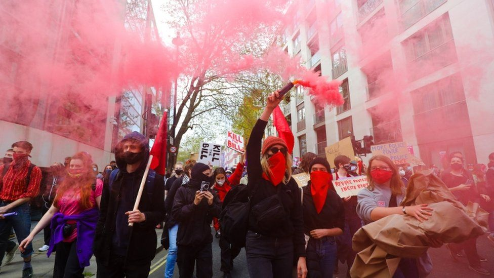 Demonstrators let off flares during a march through central London