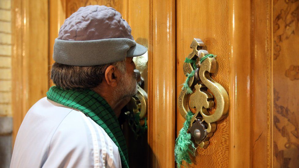 A man kisses the closed door of the Fatima Masumeh shrine in Qom