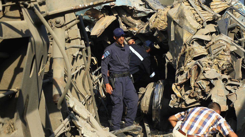 Egyptian security personnel examine wreckage after two passenger trains collided in Alexandria
