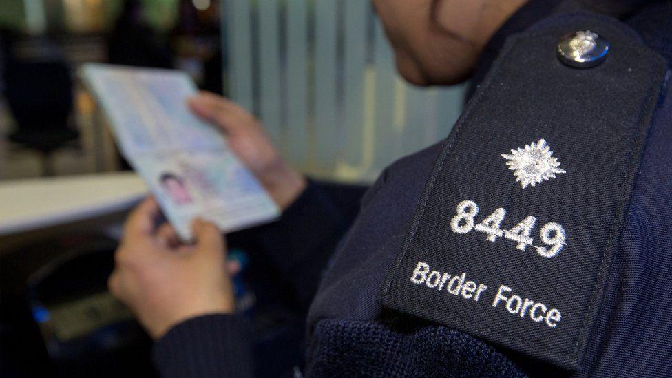 UK immigration officer checking passport