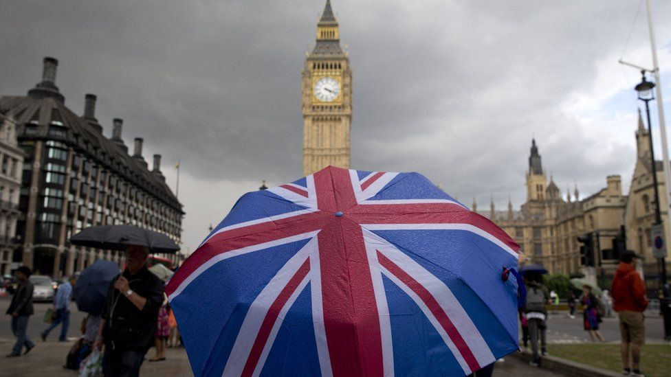 A pedestrian shelters from the rain beneath a Union flag themed umbrella as they walk near the Big Ben clock face and the Elizabeth Tower at the Houses of Parliament in central London on June 25, 2016