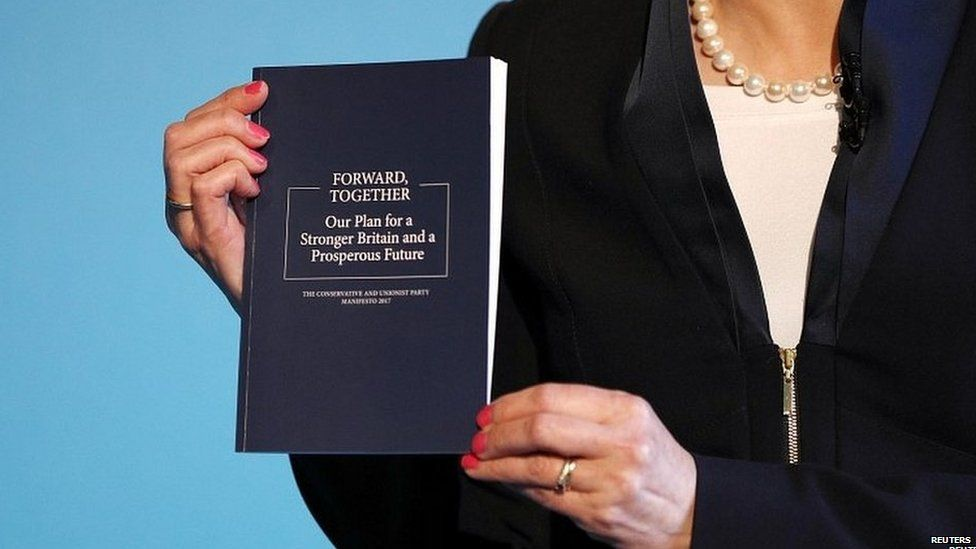 Theresa May holds copy of the Conservative party manifesto