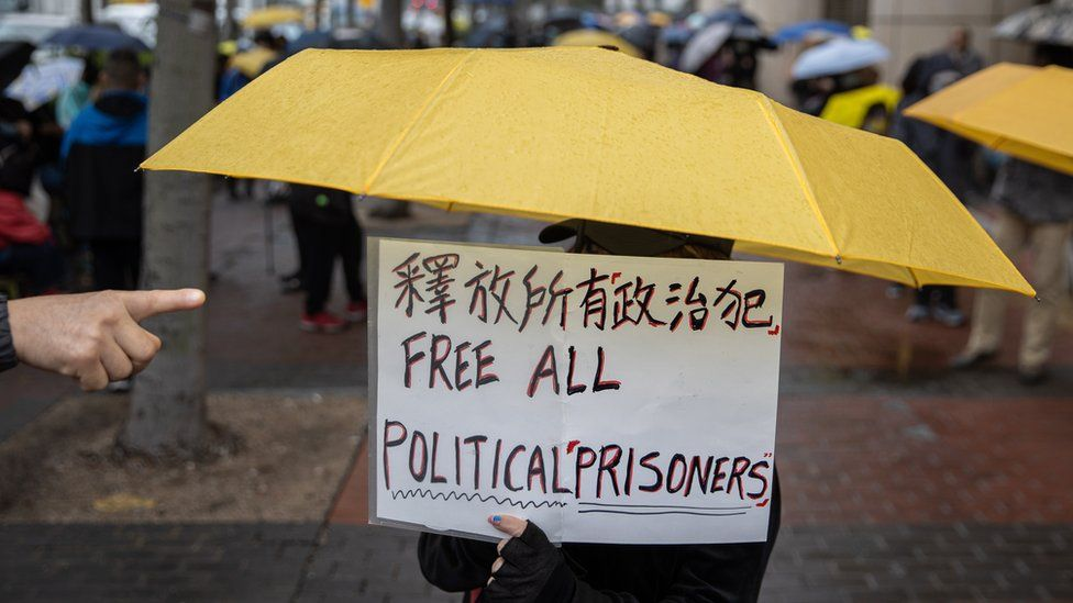 A supporter of democracy activists holds a placard while standing outside the West Kowloon court building in Hong Kong, China, 04 March 2021. A bail hearing for 47 pro-democracy figures charged with subversion has entered its fourth day. EPA/JEROME FAVRE