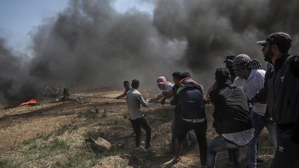 Palestinians protesters pulling barbed wire fence installed by Israeli army along the border during clashes after protests near the border with Israel in the east of Gaza Strip