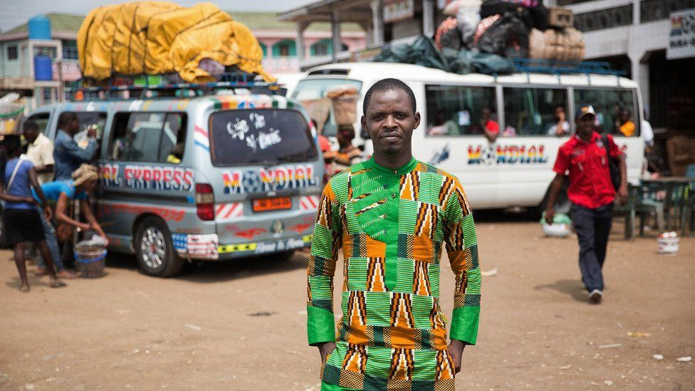 Achiri Arnold Nji stands at a bus terminal in Douala, Cameroon.