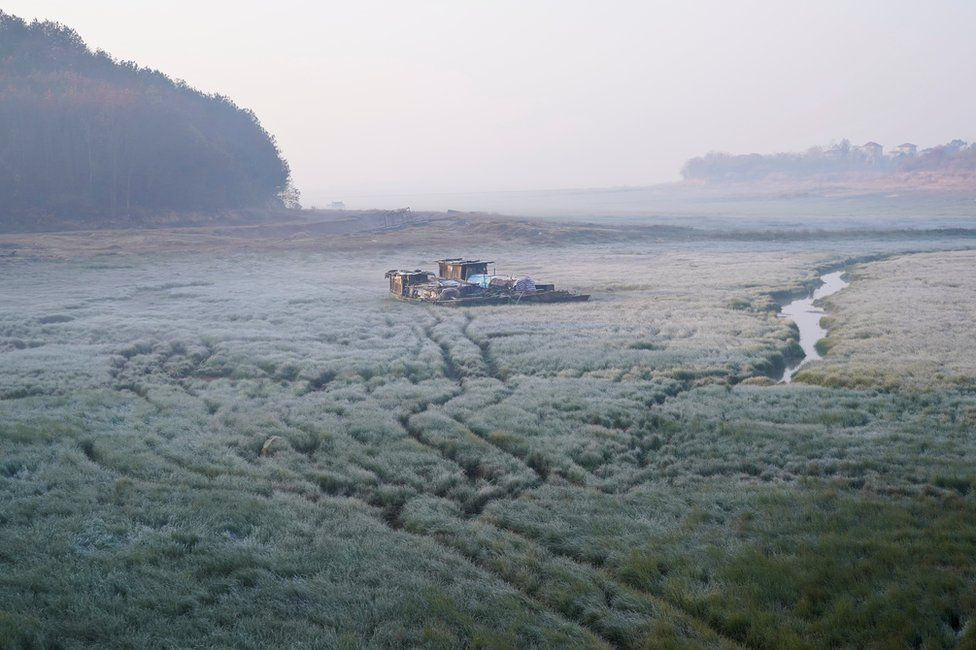 A boat sits on the dried lake bed of Poyang Lake