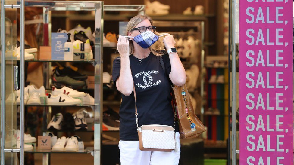 Shopper with a mask outside sale signs
