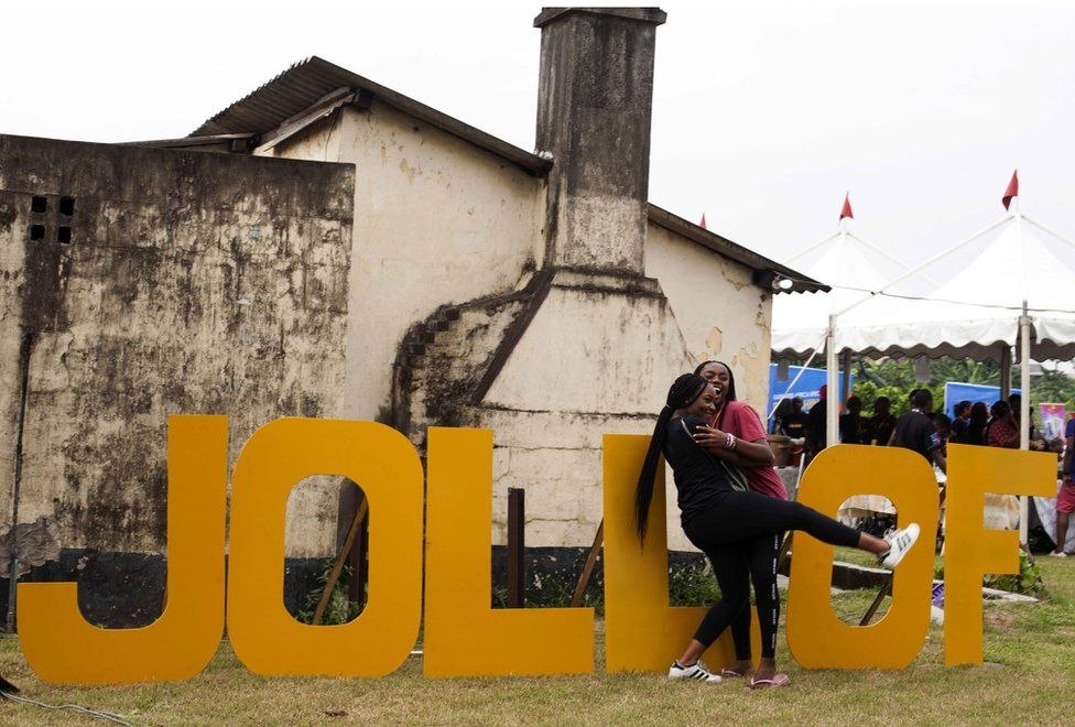 """Women hug beside letters reading """"Jollof"""", a popular dish in Nigeria and across West Africa, during the Jollof rice festival in Lagos, on August 20, 2017"""