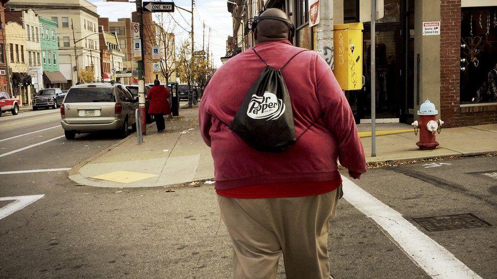 Overweight man walking across a street