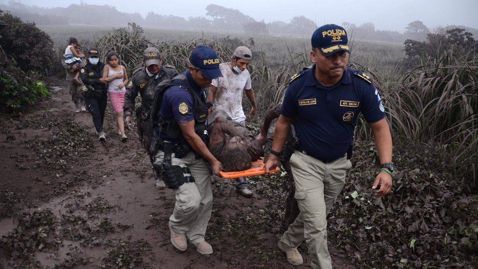 Police carry a wounded man in El Rodeo village