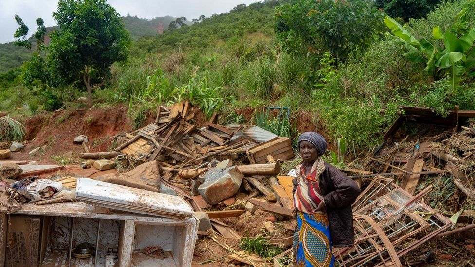 A woman stands next to her destroyed belongings on 19 March 2019, in Chimanimani, Zimbabwe