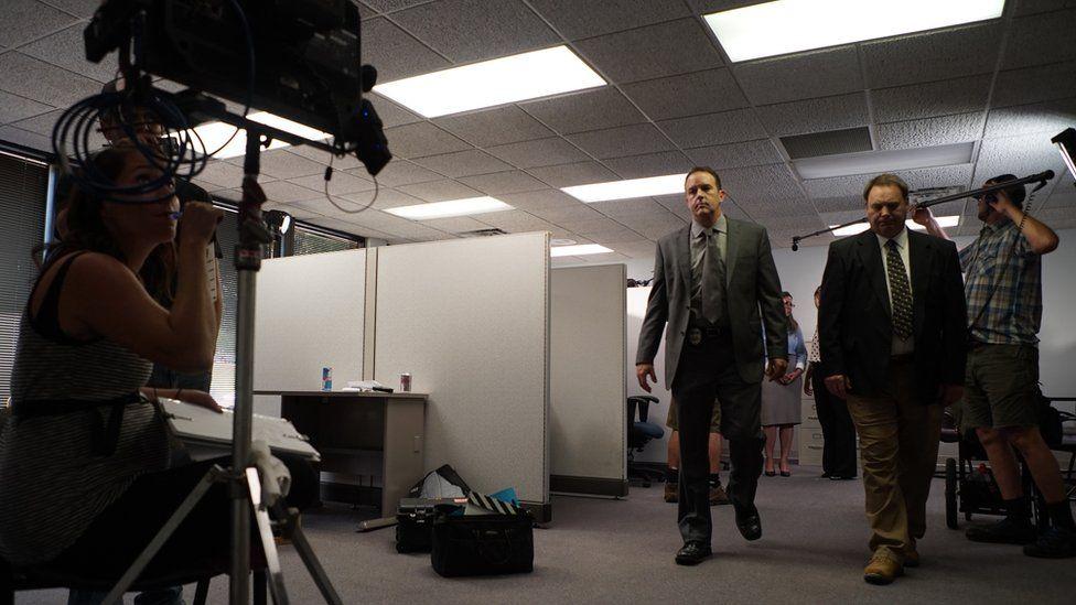 Perdenin arkasındaki çekim, oyunculara mürettebatın filme aldığı dedektif olarak gösteriyor