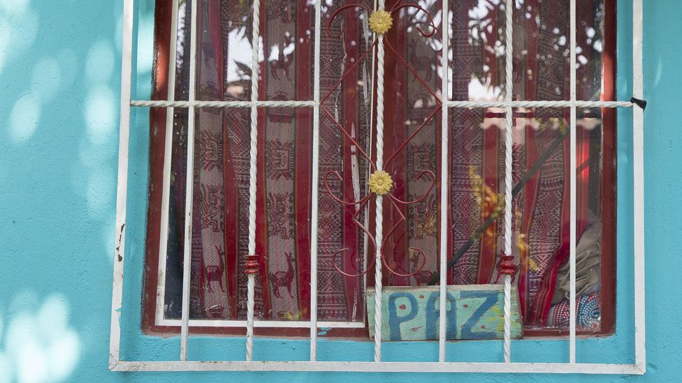 "A sign reading ""peace"" sits in the window of a home in the City of Women on 20 January, 2020."