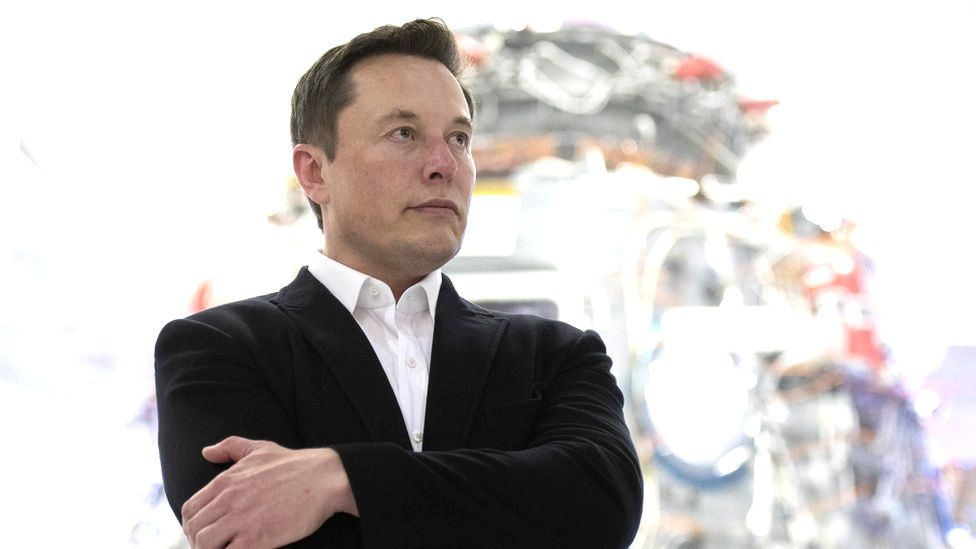 Elon Musk stands in a harshly lit room at SpaceX, in front of a hulking piece of metal and wire