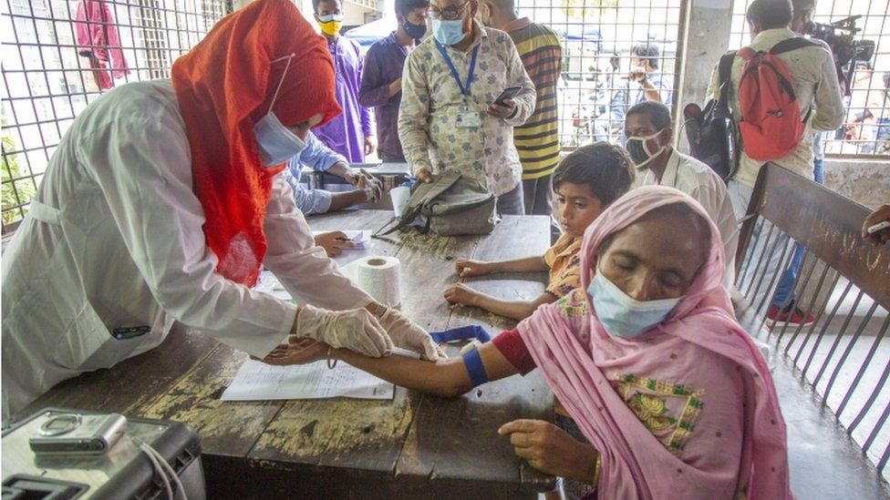 A medical officer collects blood samples from relatives of victims for DNA testing at Dhaka Medical Collage Hospital in Bangladesh, 10 July 2021