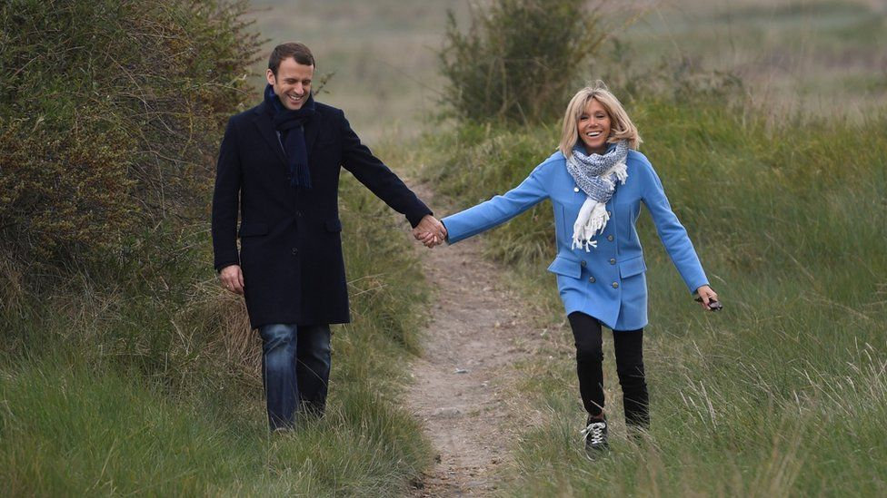 Macron and Trogneux walking on a grassy hillock