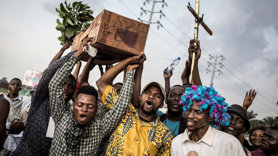 """Supporters of Martin Fayulu, the runner-up in Congolese elections, hold up a coffin with """"Good Bye Felix"""" as they protest in the street on 21 January 2019 in Kinshasa, DR Congo"""