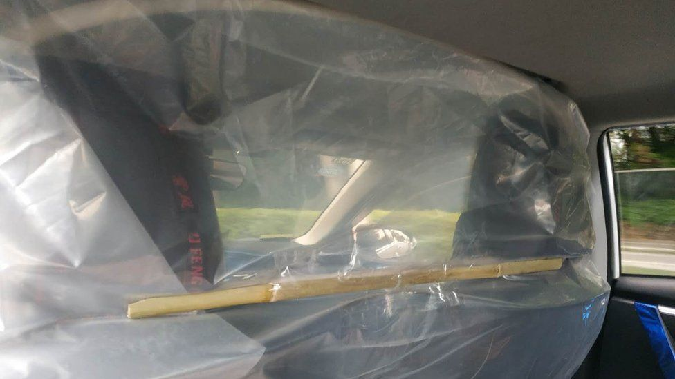 Plastic sheeting attached to car seats in a taxi