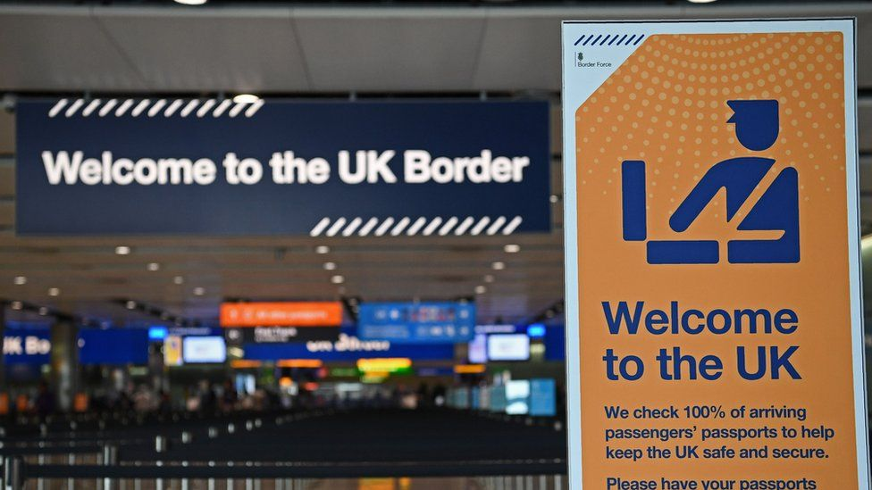 """A photo of the UK Border Control at an airport shows two signs, reading """"Welcome to the UK border"""" and """"Welcome to the UK"""", with warning about passport control"""