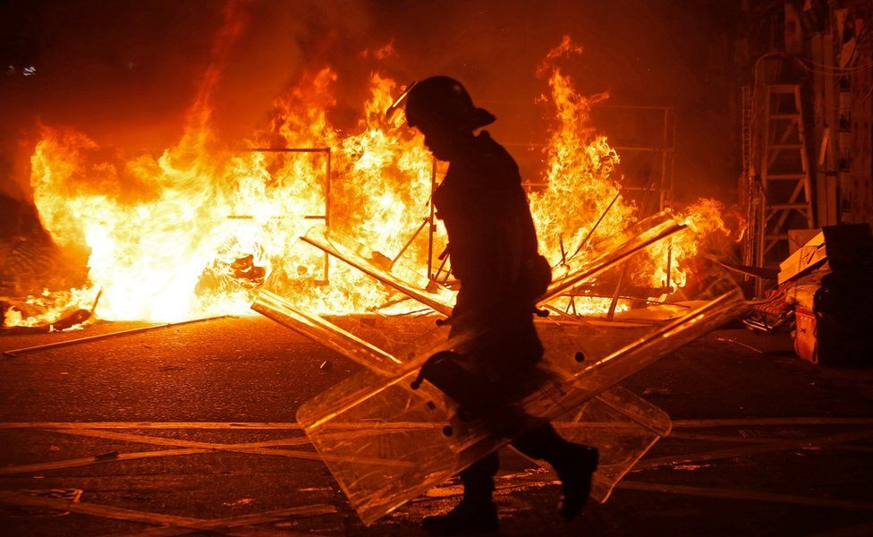 A police officer walks past a fire burning at barricades