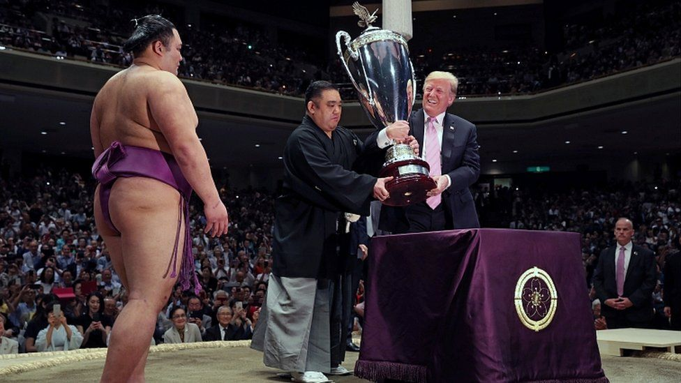 Donald Trump prepares to present the President's Cup to wrestler Asanoyama, winner of the Summer Grand Sumo Tournament at Ryogoku Kokigikan Sumo Hall in Tokyo, Japan May 26, 2019