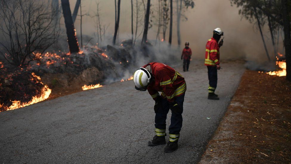 A firefighter kneels over near colleagues as they tackle a wildfire in Torredeita near Viseu, central Portugal, on 9 August 2016
