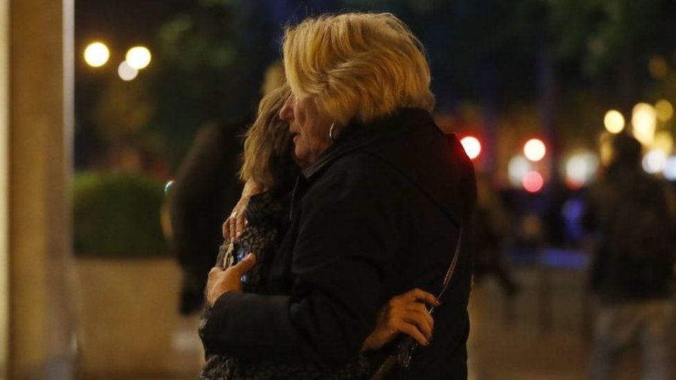 Two women hug each each other after a shooting in Paris. Photo: 20 April 2017