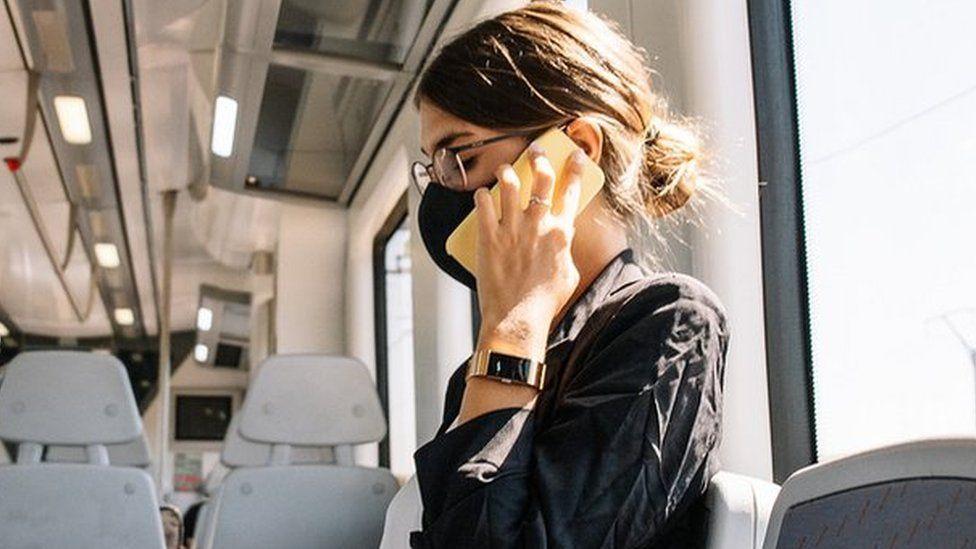 woman on empty train wearing face mask