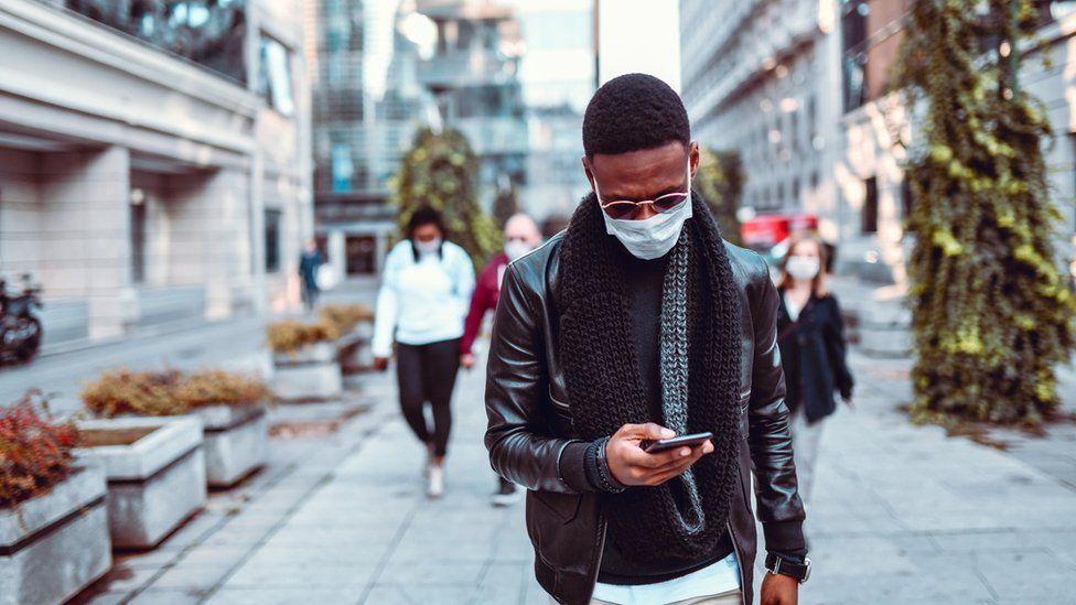 man wearing mask looking at phone