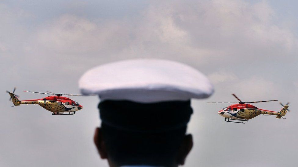 An Indian air force officer watches helicopters perform in an air show