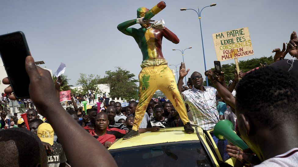 A man painted in the colours of Malian flag gestures at Independance square as protesters gather to demand that Malian President Ibrahim Boubacar Keïta leaves office in Bamako on June 19, 2020