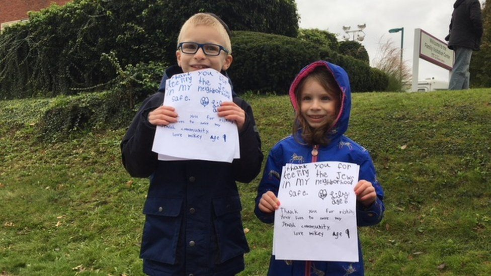 Mikey and Lily hold signs thanking the police after Pittsburgh shooting