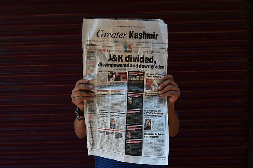 "A Kashmiri boy poses with a newspaper headline ""J&K Divided"" during curfew in Srinagar, Indian Administered Kashmir on 06 August 2019. Curfew Continues in Kashmir after the Scrapping of Article 370 on 06 August 2019. Curfew has been implemented across Jammu and Kashmir to thwart any protests. All the communication channels have been blocked across the valley. (Photo by Muzamil Mattoo/NurPhoto via Getty Images)"