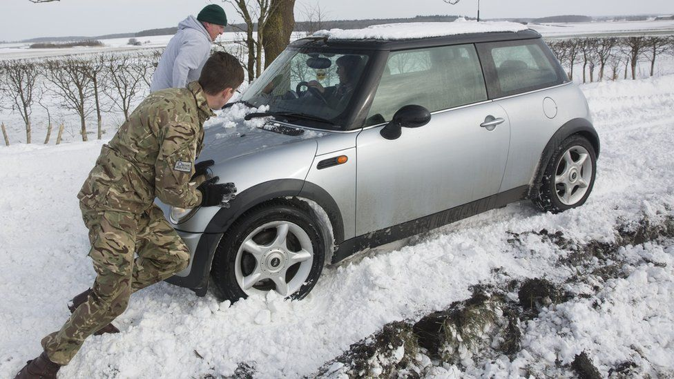 Man pushes car out of snow