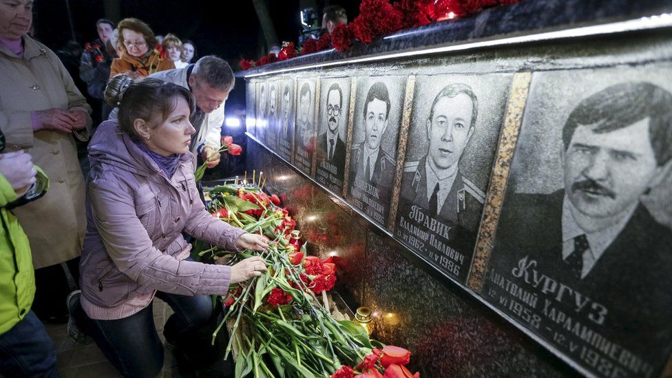 A woman lays flowers at a memorial, dedicated to firefighters and workers who died after the Chernobyl nuclear disaster, during a night service in the city of Slavutych, Ukraine, April 26, 2016.