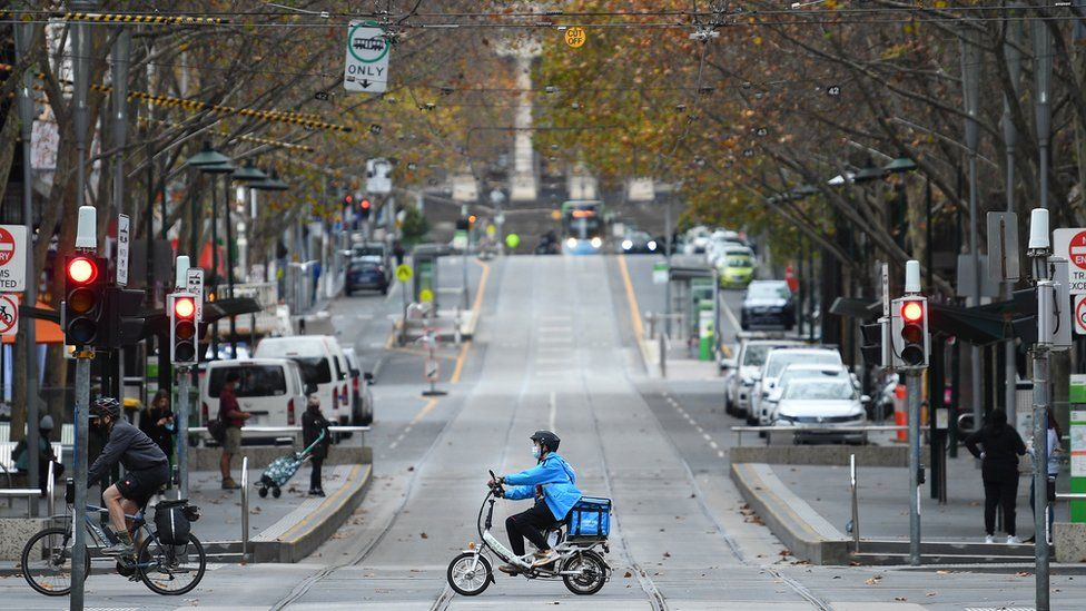 A food delivery driver drives through the deserted Melbourne city centre
