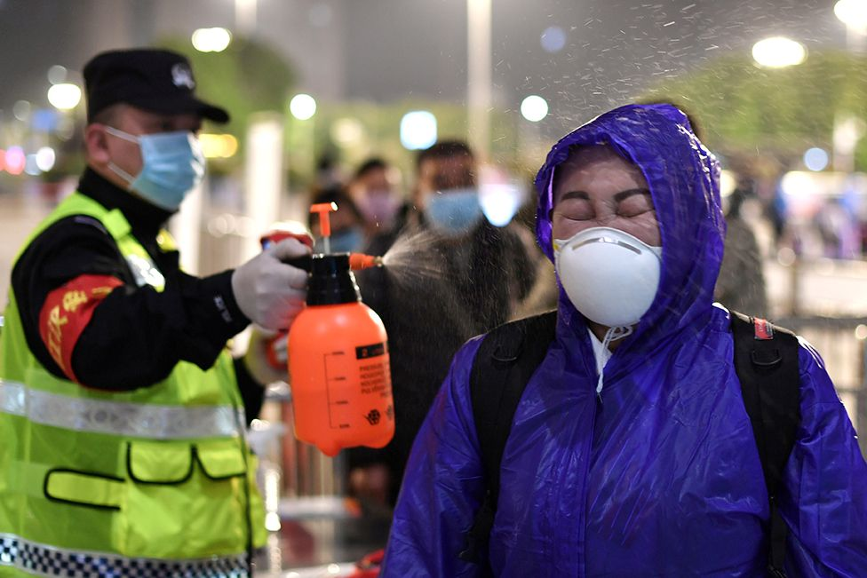A police officer sprays disinfectant on a traveller