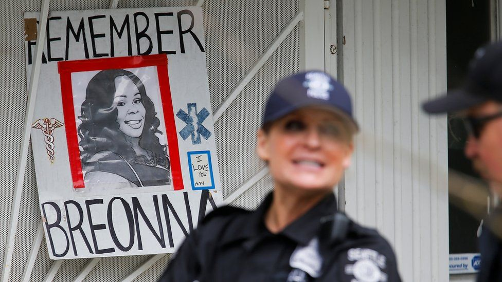 Officers stand near a sign depicting Breonna Taylor at a protest in in Seattle on 1 July 2020