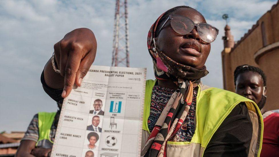 Woman holding up a ballot paper