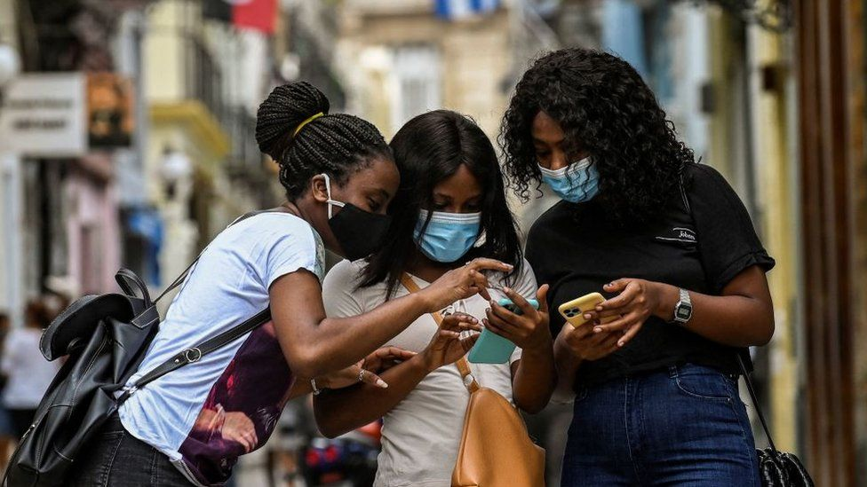 Cubans check their phones after authorities restored internet access, 14 July 2021