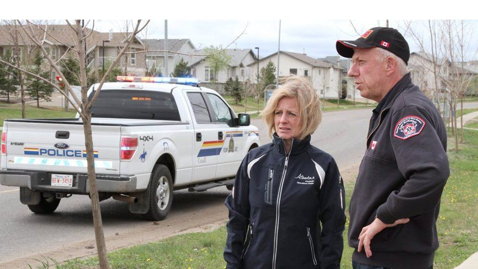 Rachel Notley and the Fort McMurray fire chief Darby Allen standing next to a police truck on an empty road