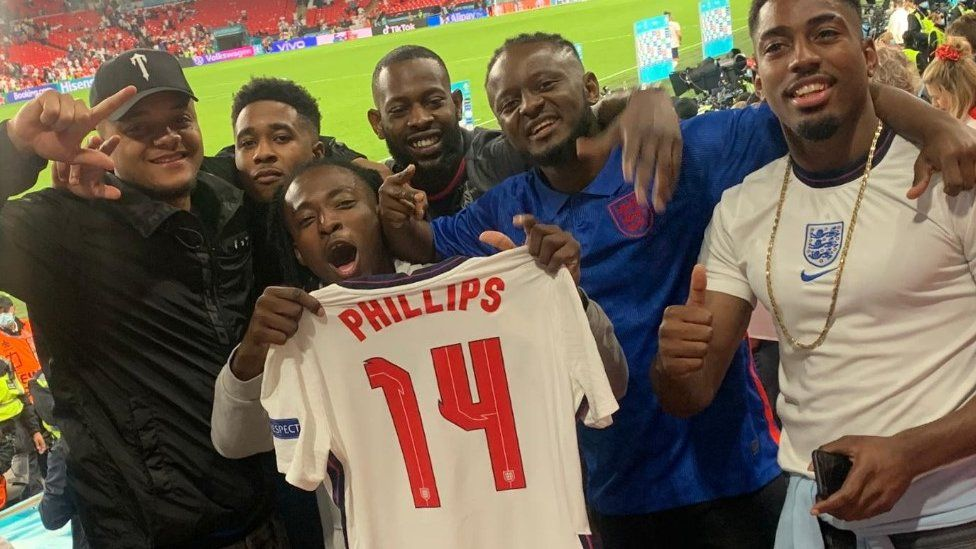 Friends of Kalvin Phillips holding his England shirt after 2-1 win over Denmark