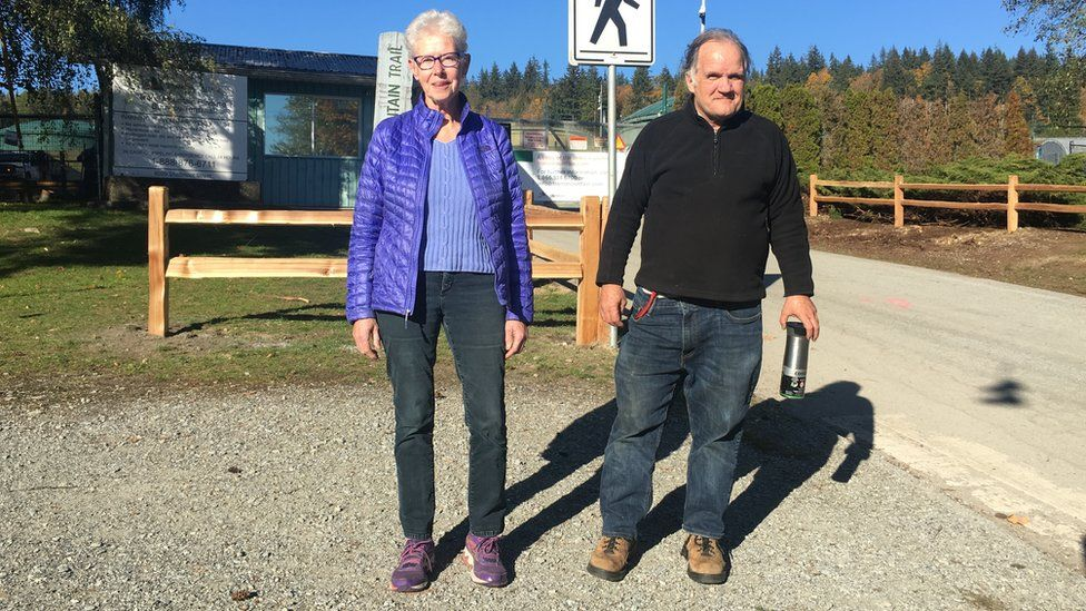 Susan Lambert and Jim Leyden stand near the Trans Mountain gates